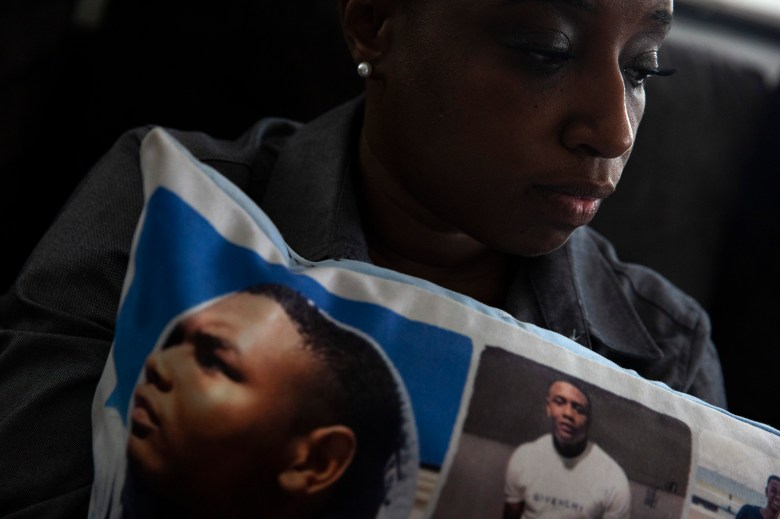 Jennifer Maraston holds a pillow covered in photos of her son Jaquan Wyatt, who was murdered the day after he turned 21 while traveling in California. It has been nearly two years since his homicide, but court proceedings have been delayed by challenges involving COVID-19 and the amount of people charged in the case. Photo by Shelby Tauber for CalMatters