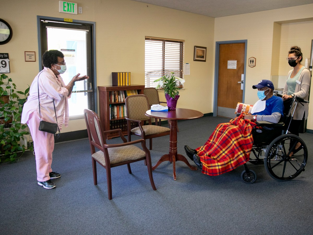 Ouida Dill, left, blows a kiss to her husband David at the end of their near-daily visit at Lincoln Glen Skilled Nursing Facility on March 29, 2021 in San Jose. David has been a resident at Lincoln Glen for more than four years and throughout the pandemic, Ouida has continued to see him almost everyday for visits through a window but now that Ouida is vaccinated they are able to see each other indoors again. Photo by Anne Wernikoff, CalMatters