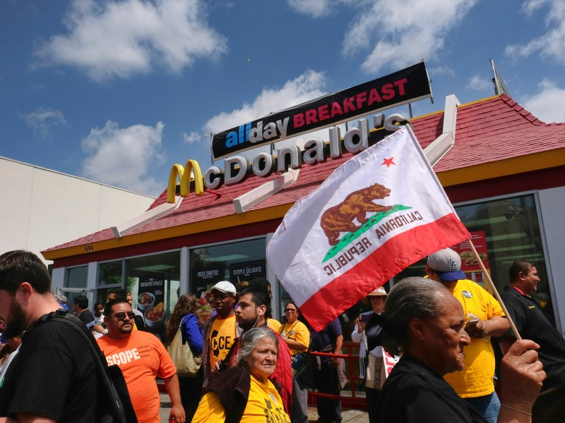 Demonstrators calling for $15 an hour and a union protest at a McDonald's restaurant in downtown Los Angeles in 2016. According to a recent report, California's economic divide has grown wider during the pandemic. Photo by Richard Vogel