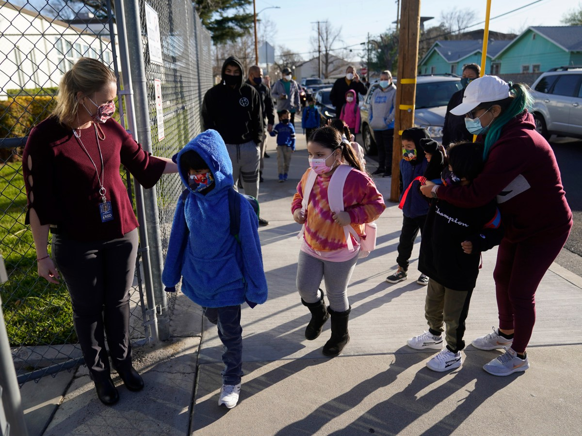 Parents drop off their childern as Assistant Principal Janette Van Gelderen, left, welcomes students at Newhall Elementary in Santa Clarita on Feb. 25, 2021. Photo by Marcio Jose Sanchez, AP Photo