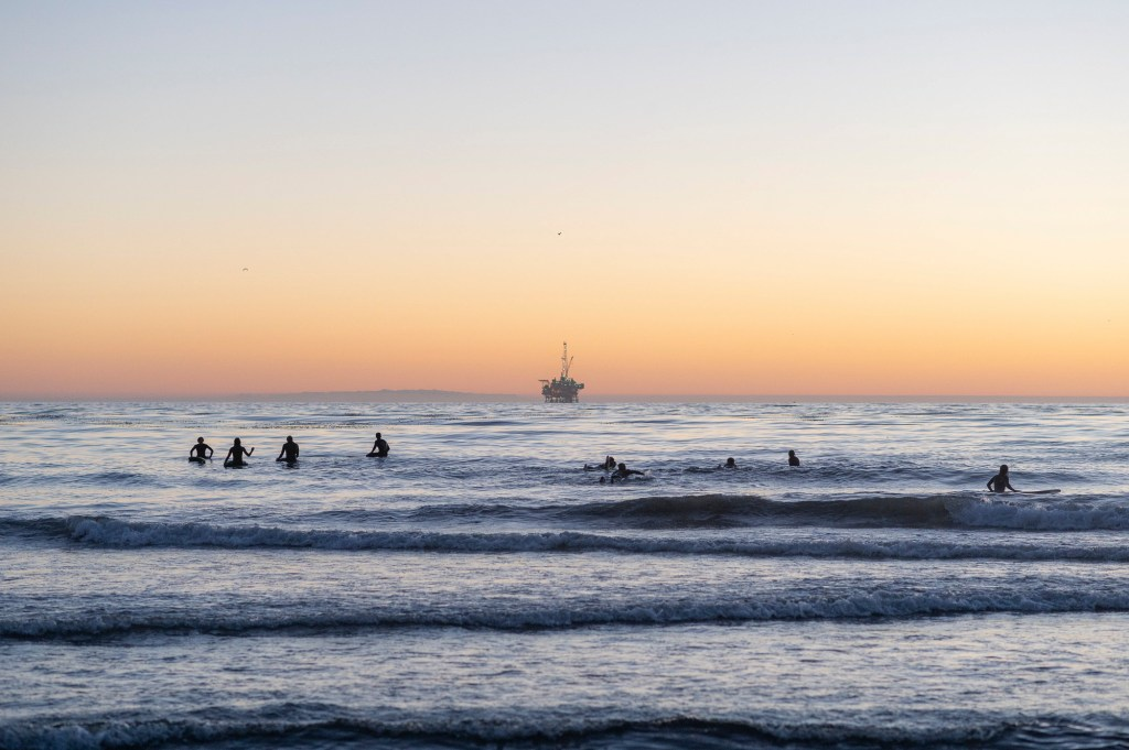 Surfers gather in the Pacific Ocean just off the coast of Coal Oil Point Reserve in Isla Vista, a popular beach for UC Santa Barbara students, on the evening of Nov. 12, 2020. Photo by Max Abrams for CalMatters
