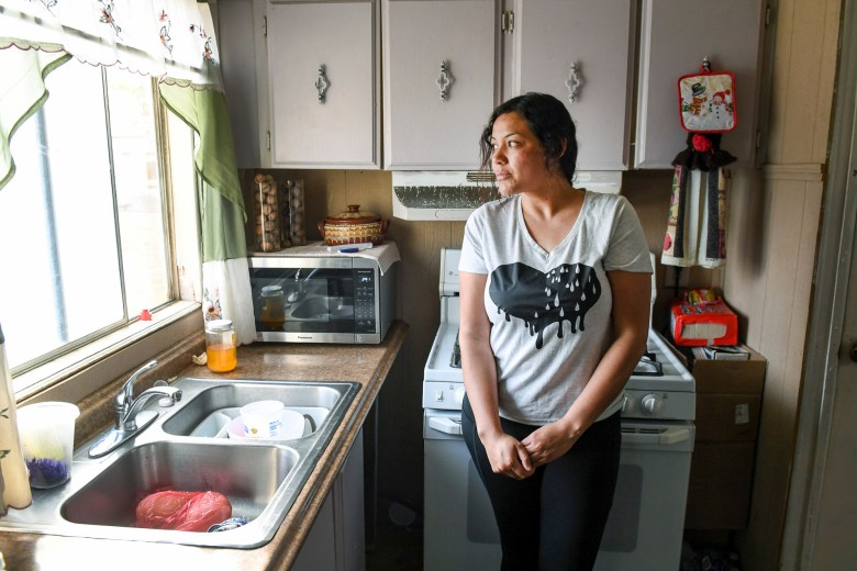 Carolina Navarro, 34, stands in the kitchen of her mobile home in Cantua Creek on March 2, 2021. Navarro is divorced with two children and has been out of work since November. Photo by Craig Kohruss, The Fresno Bee
