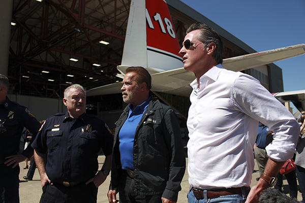 Gov. Gavin Newsom and former Gov. Arnold Schwarzenegger inspect new firefighting aircraft at McClellan Airport on Aug. 1, 2019. Photo by Barbara Harvey for CalMatters