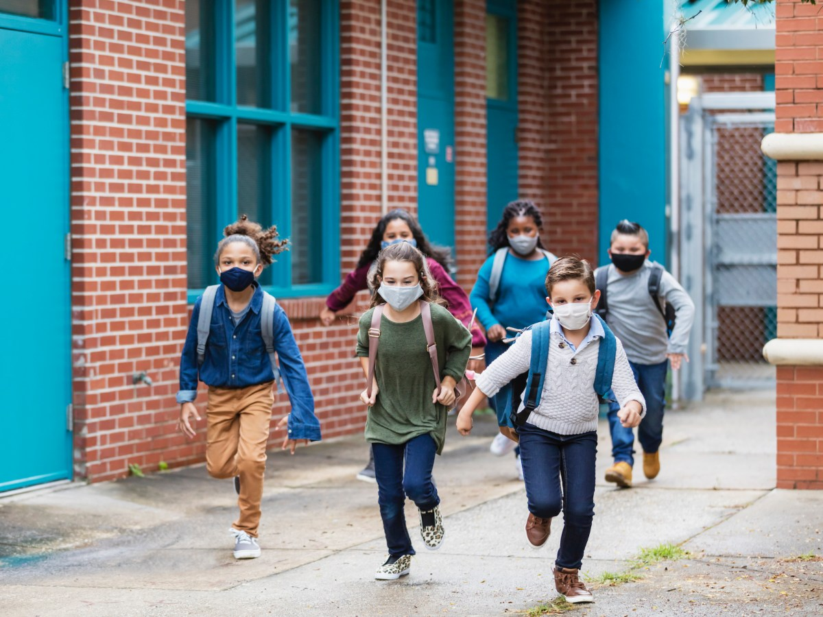 Masked children running along a school building. Some of the states biggest districts are making plans to offer free schooling options through the summer — in part to help kids catch up. Image via iStock
