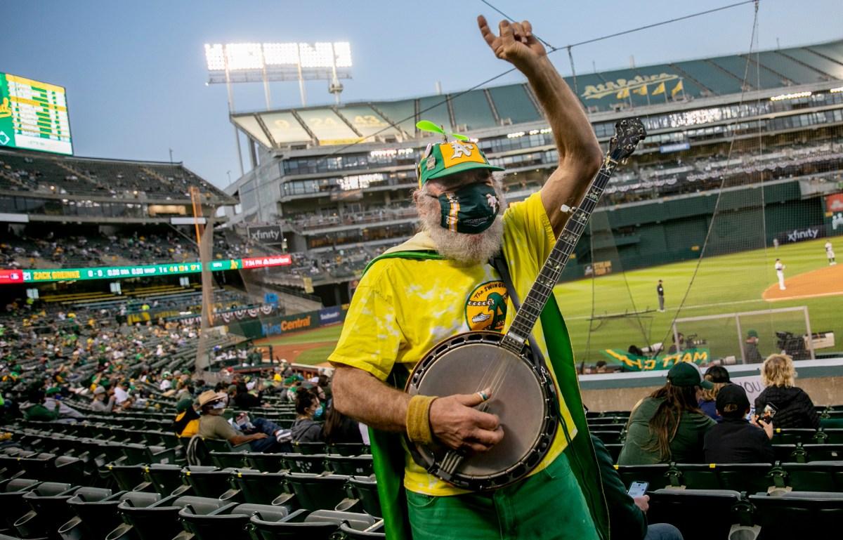 """Stacy Samuels, residente de San Francisco, también conocido como Super A o Banjo Man, toca el banjo mientras anima en las gradas. Samuels, quien ha estado llevando su banjo a los juegos de los A's durante más de 30 años, dijo: """"Es genial. Se siente como un juego regular"""", del inicio de la temporada. Foto de Anne Wernikoff, CalMatters"""