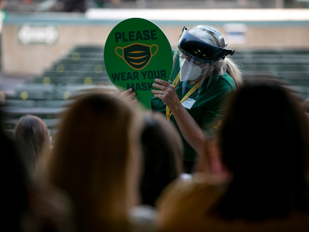 A Coliseum service employee carries a mask through the stands reminding fans to wear as mask. Coliseum implemented a number of safety protocols for the season opener including masking, distancing and touch free payments for concessions. Photo by Anne Wernikoff, CalMatters