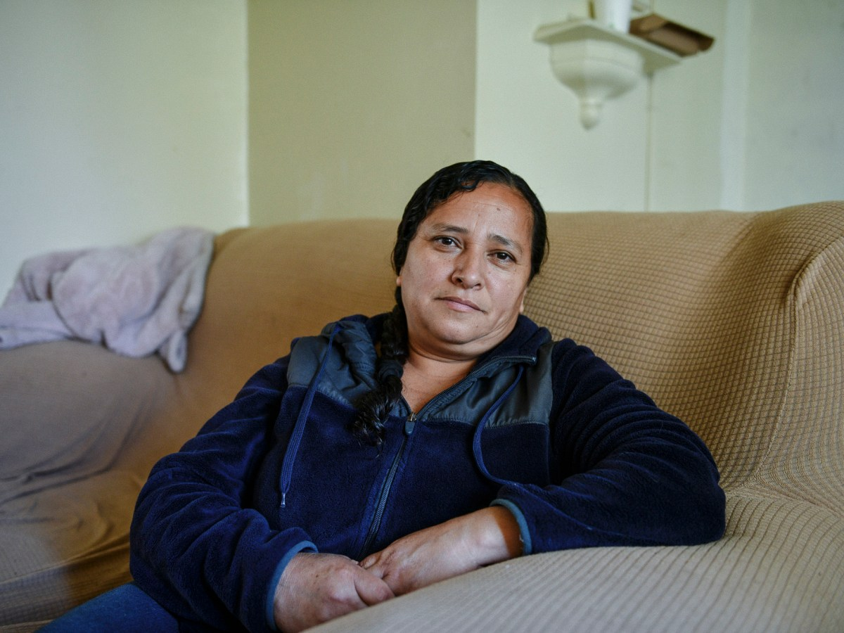 """Gladys Garcia sits for a portrait inside of her apartment at the Mar Vista Gardens public housing complex in Culver City on April 14, 2021. """"I'm afraid that when it's time to pay them the money, I'll have to leave,"""" Garcia, who is the mother of four daughters, said. Photo by Pablo Unzueta for CalMatters"""