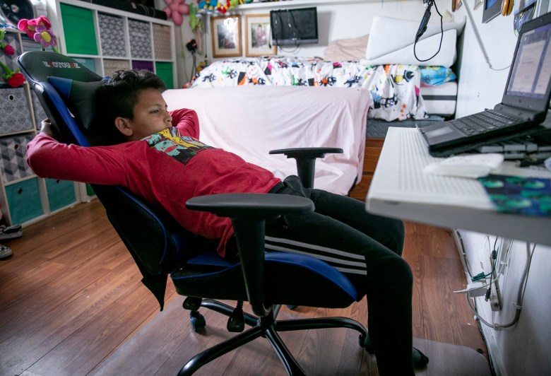 "Mario Ramirez Garcia, 10, attends online class in the bedroom he shares with his sister on April 23, 2021. ""It's funner in real school,"" said Mario of distance learning. Photo by Anne Wernikoff, CalMatters"