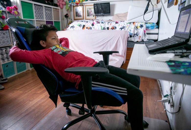 """Mario Ramírez García, de 10 años, asiste a una clase en línea en el dormitorio que comparte con su hermana el 23 de abril de 2021. """"Es más divertido en la escuela real"""", dijo Mario sobre la educación a distancia. Foto de Anne Wernikoff, CalMatters"""