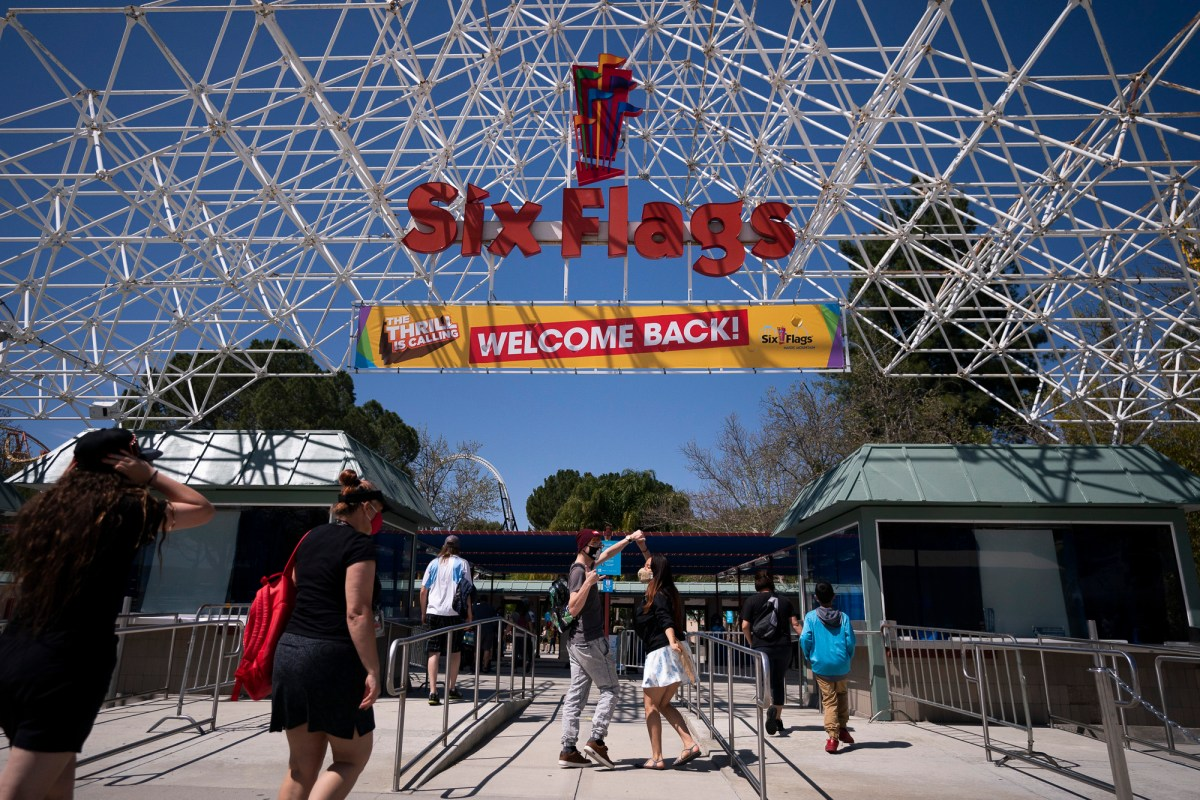 """Two visitors jokingly dance as they walk underneath a """"Welcome Back"""" sign at Six Flags Magic Mountain on its first day of reopening to members and pass holders in Valencia April 1, 2021. Photo by Jae C. Hong, AP Photo"""