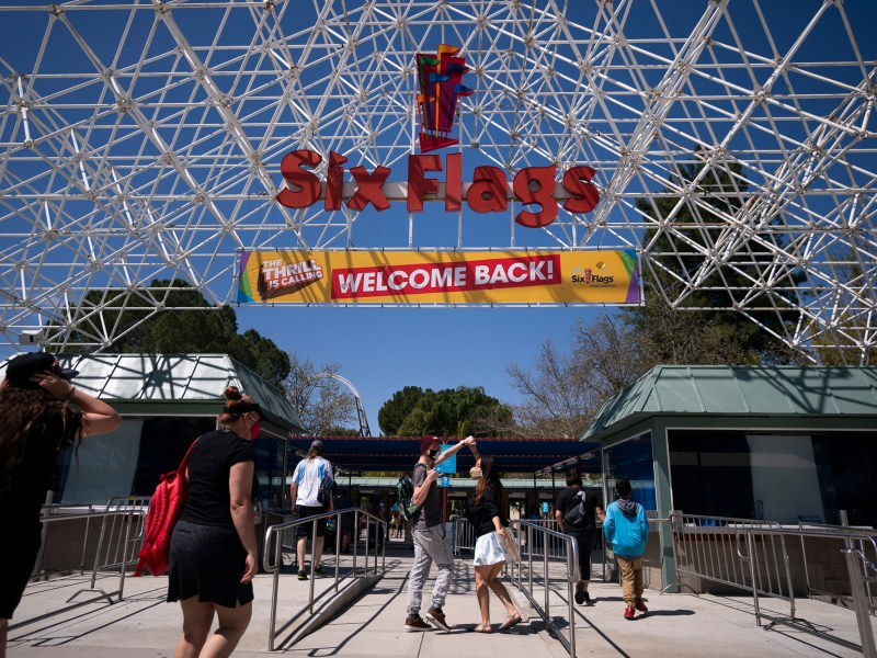 "Two visitors jokingly dance as they walk underneath a ""Welcome Back"" sign at Six Flags Magic Mountain on its first day of reopening to members and pass holders in Valencia April 1, 2021. Photo by Jae C. Hong, AP Photo"