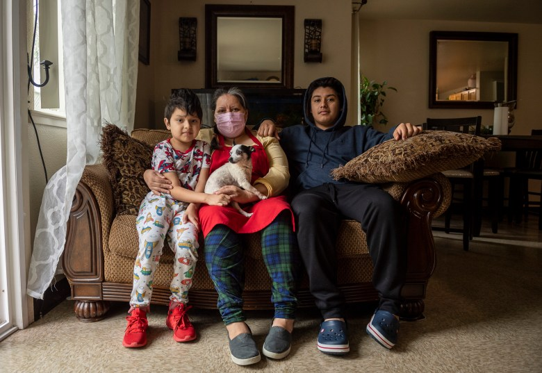 Dylan Domingo, 8, sits next her mother Blanca Esthela Trejo, center, and his older brother Illian Domingo, 18, inside their home in Salinas on April 22, 2021. Photo by David Rodriguez, The Salinas Californian
