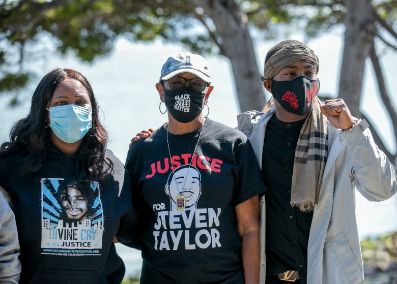 Wanda Johnson, left, Addie Kitchen and Stevante Clark pose for a group photo at a celebration of life held for Steven Taylor on the one-year anniversary of his death, at the San Leandro Marino on April 18, 2021. Photo by Anne Wernikoff, CalMatters