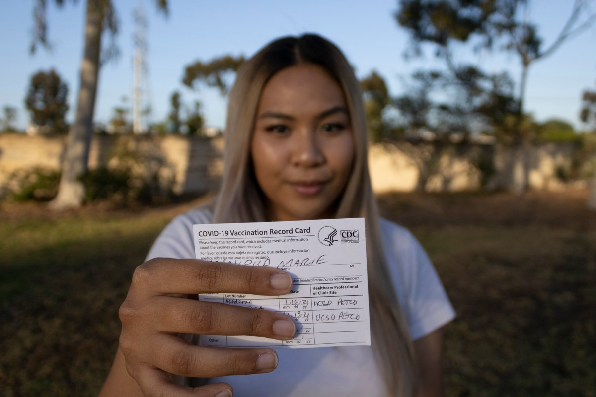 Marie Manipud holding her COVID-19 vaccination card at Lindbergh Neighborhood Park on May 4, 2021. UC San Diego students are able to attend an in-person graduation this year with a negative COVID test or proof of vaccination. Photo by Arlene Banuelos for CalMatters.