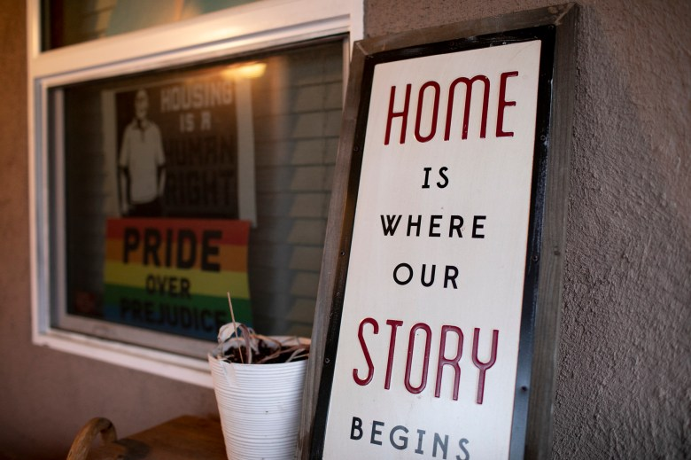 Signs on the front porch of Merika Reagan's Oakland home depicting support for housing rights and gay pride. Photo by Anne Wernikoff, CalMatters