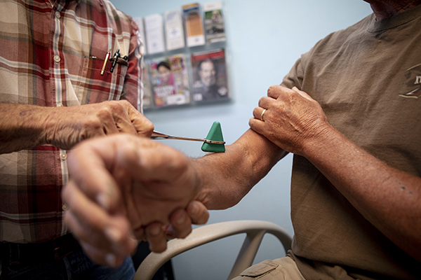 A man has his reflexes tested at a clinic in Bieber, California on July 23, 2019. Photo by Anne Wernikoff for CalMatters