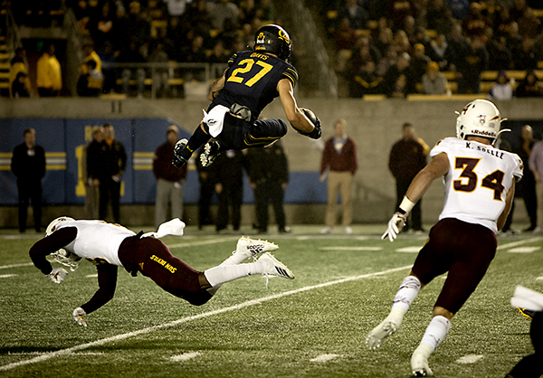 Cal safety Ashtyn Davis leaps over an opponent while running the ball during the Cal vs ASU game at Memorial Stadium on September 27, 2019. Photo by Anne Wernikoff for CalMatters