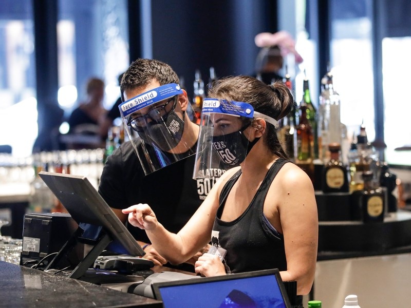 Bartenders were masks and face shields as they work at Slater's 50|50 on July 1, 2020, in Santa Clarita. Photo by /Marcio Jose Sanchez, AP Photo