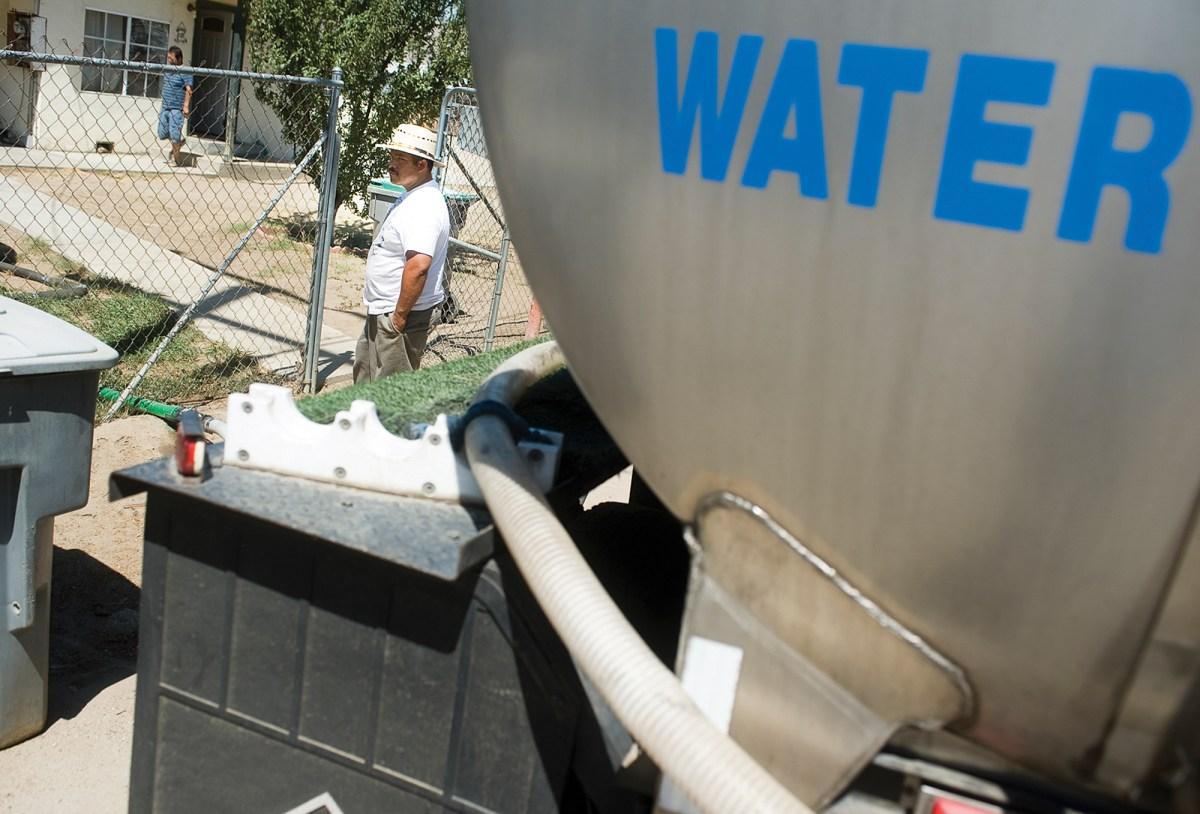 """Las comunidades rurales latinas se vieron muy afectadas por la última sequía de California. Aquí """"Aqua Man"""" Sebastian Mejia entrega agua a las casas en el área de East Porterville en 2015. Foto de Chieko Hara, The Porterville Recorder vía AP"""