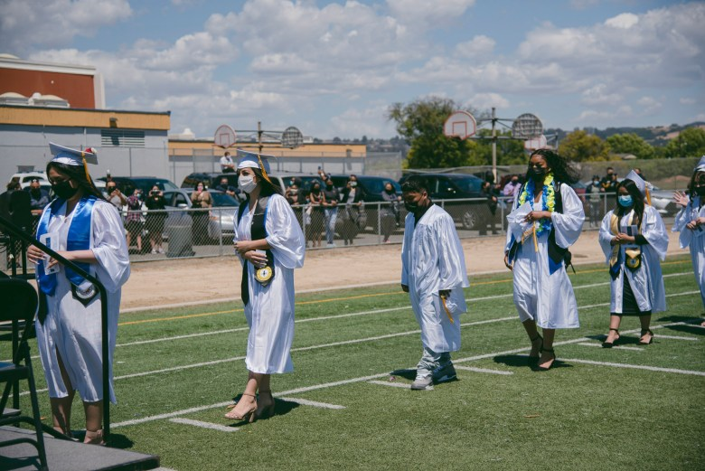 Graduates line up to receive their diplomas during a commencement ceremony at Madison Park Academy in Oakland on May 21, 2021. Photo by Marissa Leshnov for CalMatters