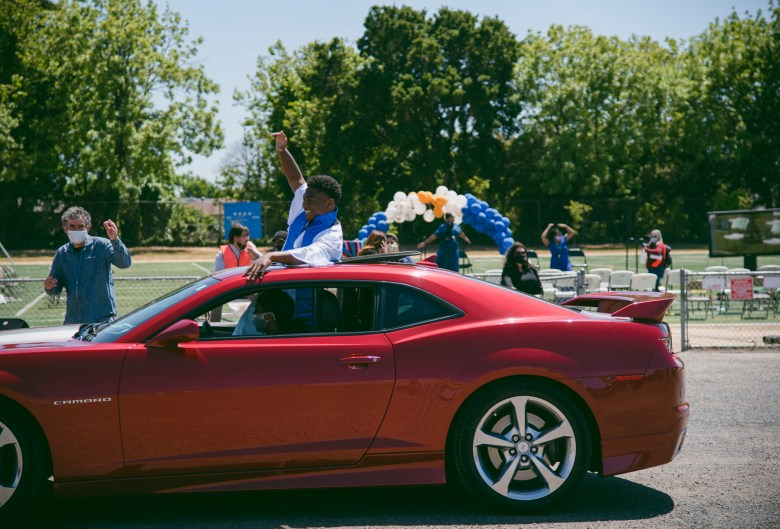 Sir cheers from the sunroof of a car while driving away to make room for the following commencement ceremony at Madison Park Academy on May 21, 2021. Photo by Marissa Leshnov for CalMatters