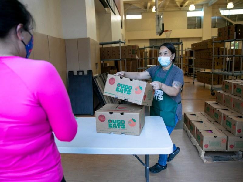 La gerente de servicio de alimentos Nakheu Saephanh entrega cajas de comida a los miembros de la familia en La Escuelita en Oakland el 7 de junio de 2021. El Distrito Escolar Unificado de Oakland ha estado proporcionando cajas para recoger o entregar que contienen siete días de desayuno, almuerzo y refrigerios a todos los estudiantes desde la primavera 2020. Foto de Anne Wernikoff, CalMatters