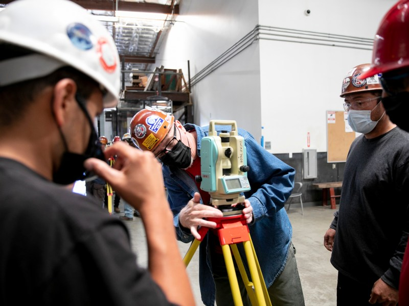 Apprenticeship instructor Mike Miller, center, demonstrates how to set up a theodolite, a hyper-sensitive angle measuring device, for apprentices Daniel Rivas, left, Ivan Aguilar, right, and Quetzalcoatl Orta, far right, at Iron Workers union in Benicia on June 10, 2021. Photo by Anne Wernikoff, CalMatters