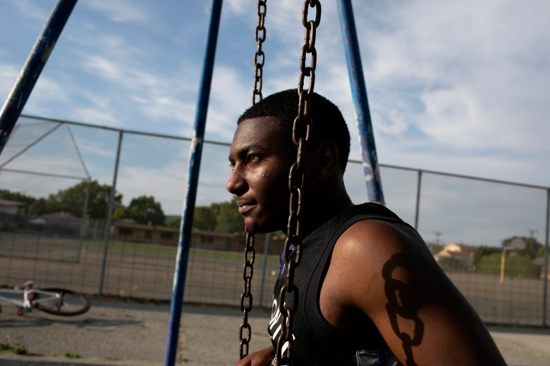 Sir sits on the swings at Sobrante Park behind Madison Park Academy. Photo by Anne Wernikoff, CalMatters