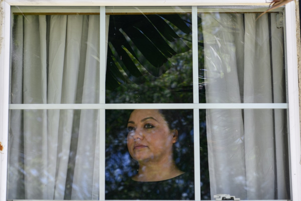 """Graciela Gomez looks out the window from her boyfriend's home in South Gate. """"One Sunday I'm home and I get served,"""" Gomez said. """"One of the credit card companies had sued me."""" Photo by Pablo Unzueta for CalMatters"""