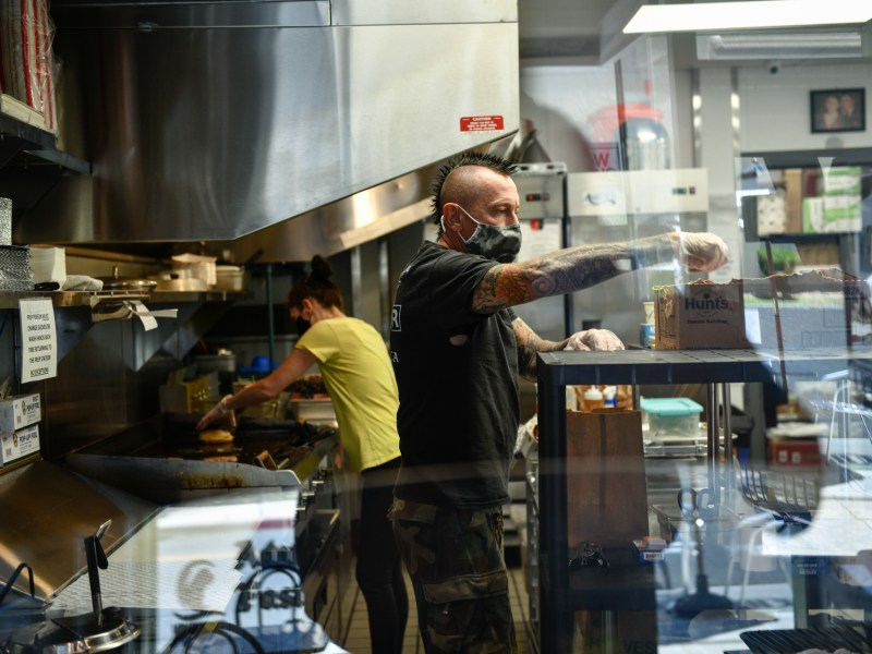 """Alex Armstrong, 51 and his wife, Paula Armstrong, 45, prepare pick up orders during lunch hour at their Long Beach restaurant, VBurger, on June 8, 2021. """"It's been very challenging for us, but we couldn't back out,"""" said Armstrong of opening mid-pandemic last year. Photo by Pablo Unzueta for CalMatters"""
