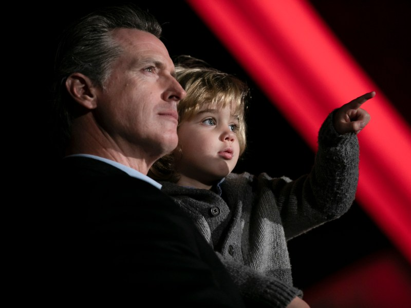 Gov. Gavin Newsom with his youngest son, Dutch, during the annual Christmas tree lighting at the Capitol on December 15, 2019. Photo by Anne Wernikoff, CalMatters