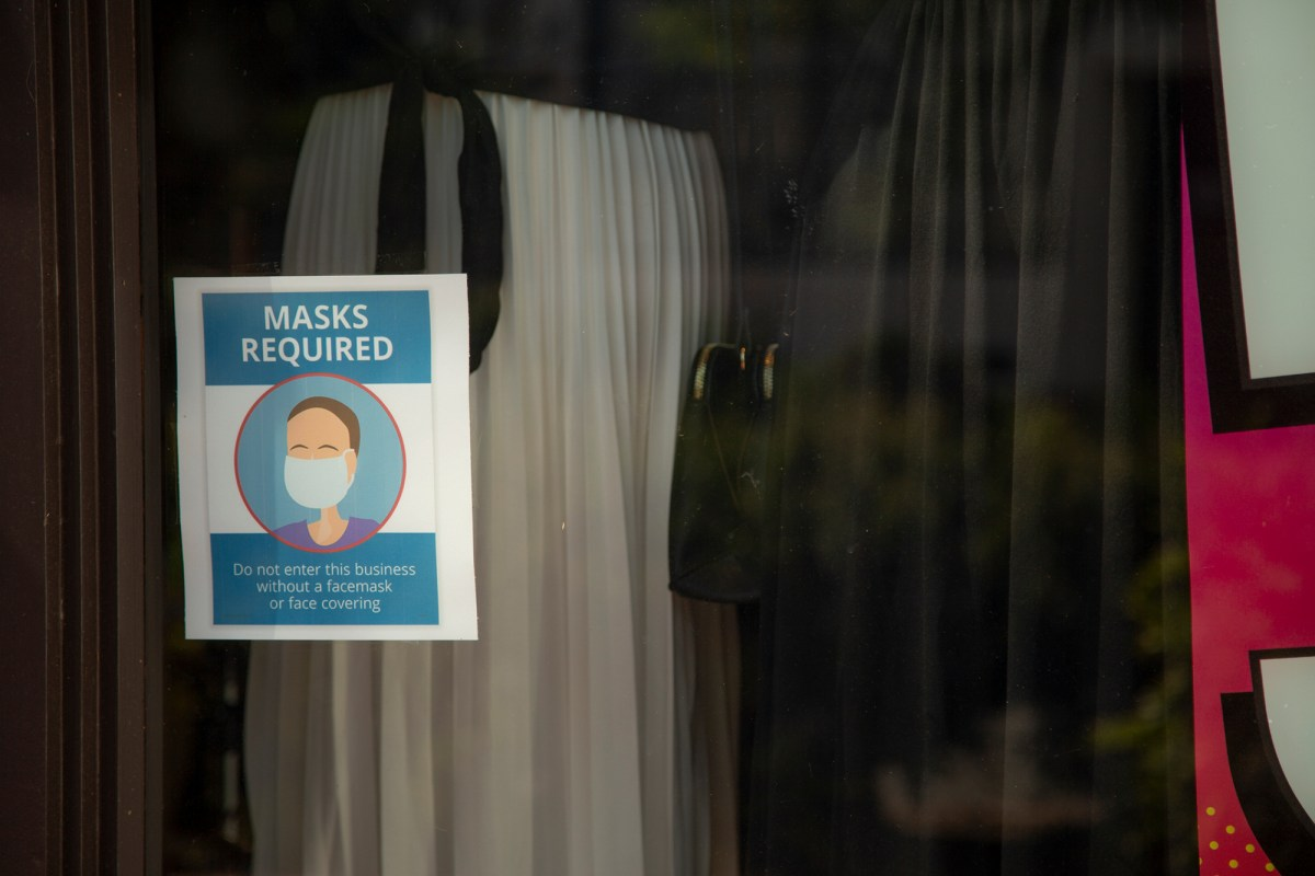 A sign warns people to mask up. Questions abound ahead of California's pandemic reopening. Image via iStock