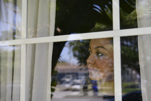 """Graciela Gomez looks out the window from her boyfriend's home in South Gate, on June 28, 2021. """"One Sunday I'm home and I get served,"""" Gomez said. """"One of the credit card companies had sued me."""" According to Gomez, that's when she realized that ClearOne Advantage, a debt relief company, wasn't helping her recover from debt, despite Gomez paying ClearOne Advantage $250 dollars a month for their advertised services. Pablo Unzueta for CalMatters"""