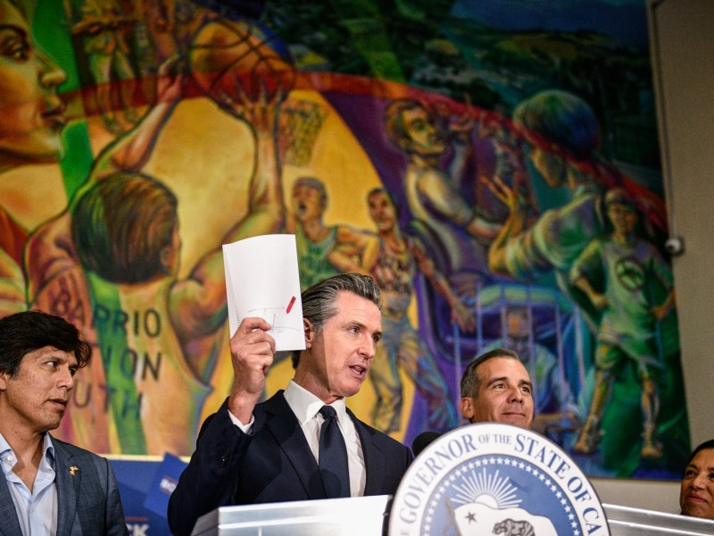 Gov. Gavin Newsom holds up the California Comeback Plan relief bill after signing it alongside Los Angeles City councilman Kevin de Leon, left, and Los Angeles Mayor Eric Garcetti at the Barrio Action Youth and Family Center in El Sereno, on July 13, 2021. Pablo Unzueta for CalMatters