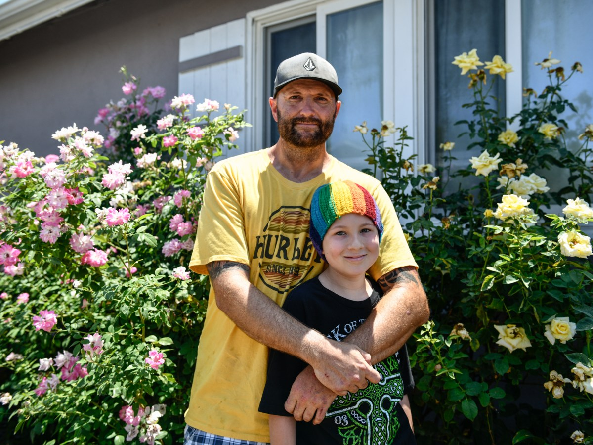 """Will Hollman with his son outside of his home in the San Fernando Valley. """"I love my kids and it is my duty to be a parent,"""" Hollman said. """"I'm fighting a lot of battles."""" Pablo Unzueta for CalMatters"""