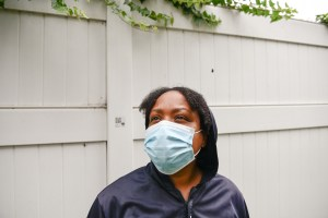 Rasheena McCord stands outside the hotel in Long Beach where McCord and her kids are living, on July 26, 2021. According to McCord, she has had to sleep on park benches after getting evicted one year ago. Housing Long Beach has assisted McCord in finding temporary housing. Photo by Pablo Unzueta for CalMatters