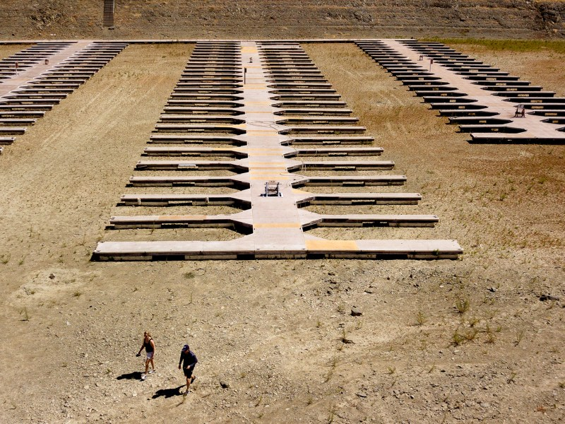 People walk near boat docks as they sit on dry land at the Browns Ravine Cove area of drought-stricken Folsom Lake, currently at 37% of its normal capacity, in Folsom on May 22, 2021. California Gov. Gavin Newsom declared a drought emergency for most of the state. Photo by Josh Edelson, AP Photo