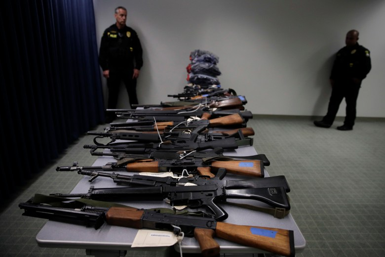 Two police officers stand near illegally possessed firearms seized by authorities during a news conference in 2018, in Los Angeles. California Attorney General Xavier Becerra and Los Angeles County Sheriff Jim McDonnell announced a joint operation designed to remove illegally possessed weapons and ammunition from individuals registered in the Armed Prohibited Persons System database. Photo by Jae C. Hong, AP Photo