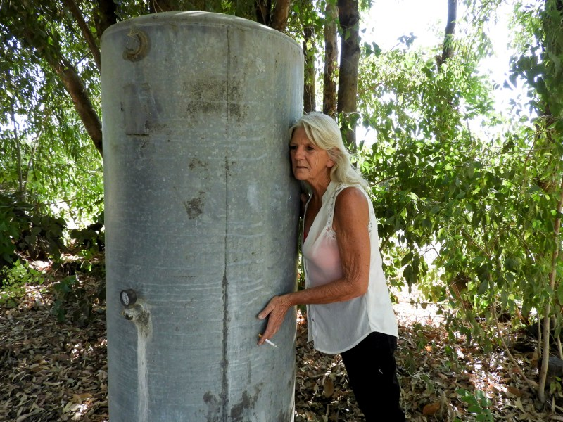 Kelly O'Brien listens to her well hum as it fills with cool water after more than a month of living without water, at her home on July 2, 2021. Photo by Rachel Becker, CalMatters
