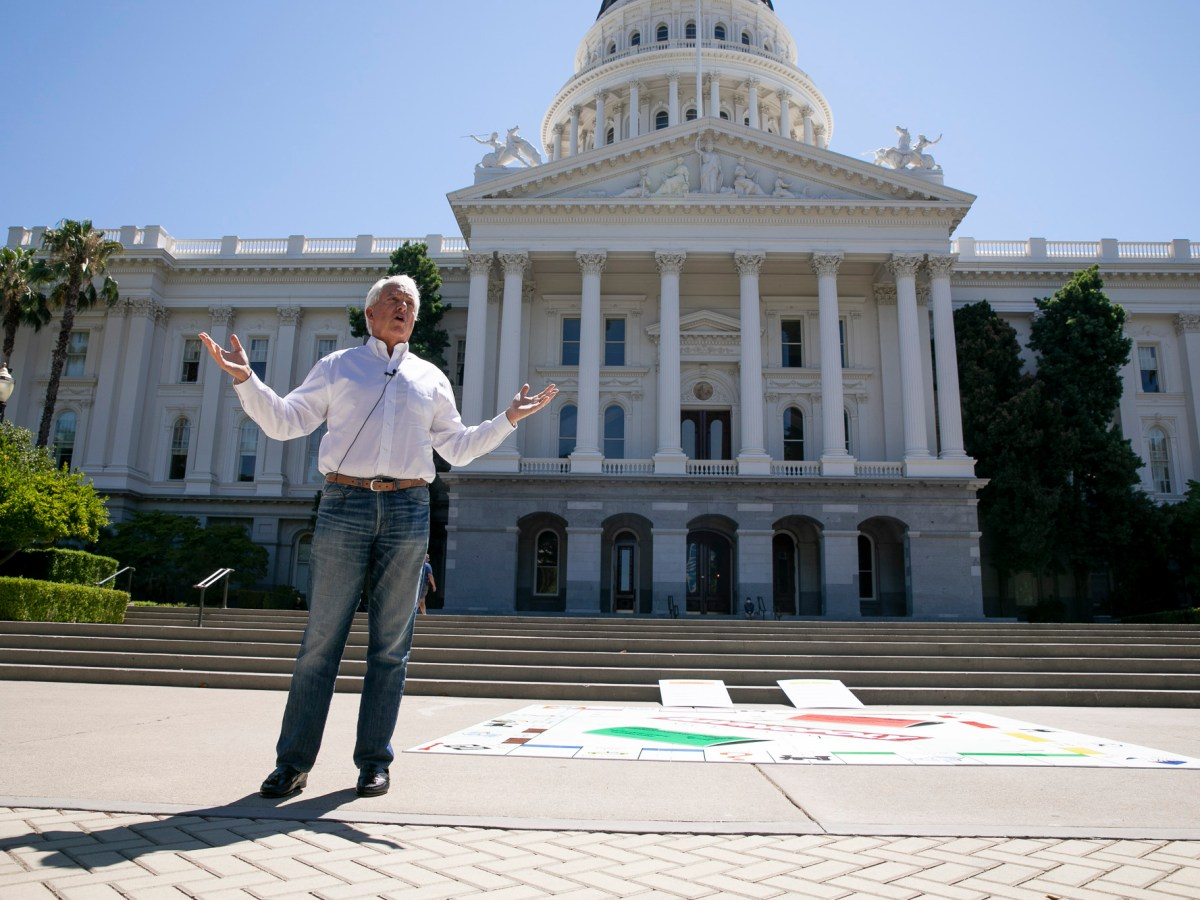 """Republican recall candidate John Cox holds a press conference at the state Capitol on Aug. 5, 2021. Cox brought a giant Monopoly board dubbed """"Gavinopoly"""" to outline points in his proposed tax cut plan. Photo by Anne Wernikoff, CalMatters"""