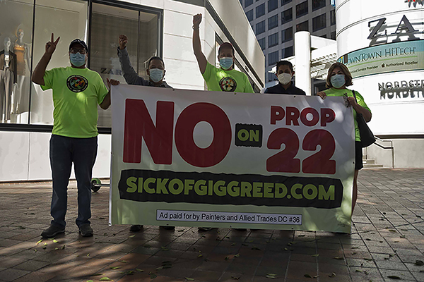 """Members of Rideshare Drivers United, Eduardo Romero, Oscar Rodriguez, Alejandro Partida, Nixon Diaz, and Norma Bustamante hold up a """"No on Prop 22"""" sign in downtown Los Angeles on Oct. 31, 2020. Photo by Tash Kimmell for CalMatters."""