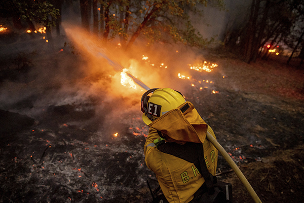 A firefighter hoses down flames from the Dixie Fire in Genesee on Aug. 21, 2021. Photo by Ethan Swope, AP Photo