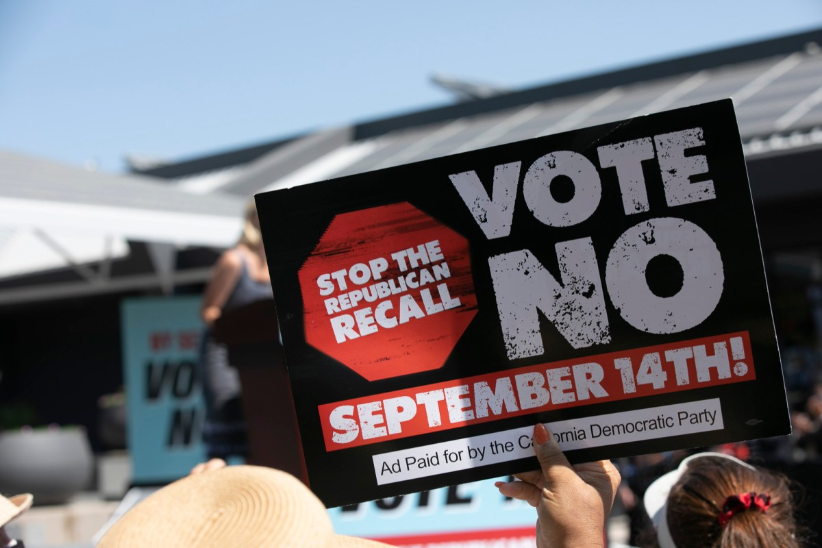 """Gov. Gavin Newsom supporters hold up signs urging voters to vote """"no"""" on the recall ballot during a campaign event for the Governor at the IBEW-NECA training center in San Leandro on Sept. 8, 2021. Photo by Anne Wernikoff, CalMatters"""