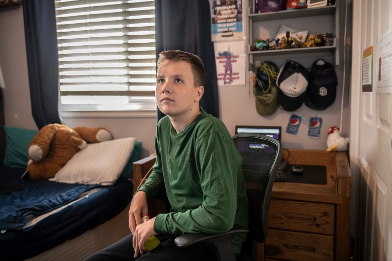 """Jack watches a video related to his schoolwork in Monrovia, on Sept. 15, 2021. """"There is no way to go back with 37 kids in a classroom,"""" Julie Fitzgibbons, the mother of triplets, said. """"With masks and not being able to communicate very well, and autism, there is just no way we can go back like normal."""" Photo by Pablo Unzueta for CalMatters"""