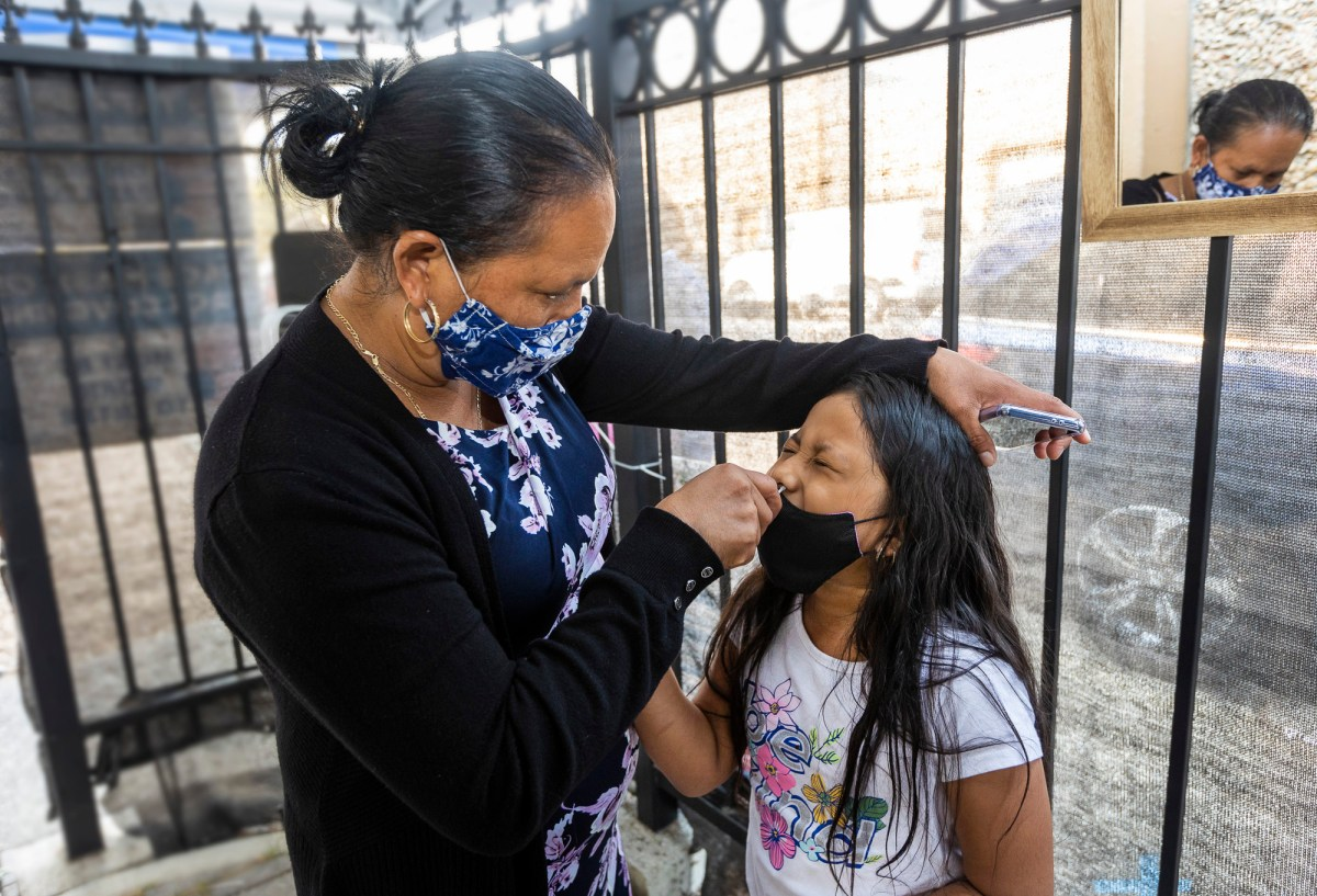 Maria Jimenez swabs her 7 year old daughter, Glendy Perez, for a COVID-19 test at Canal Alliance in San Rafael on Sept. 25, 2021. Photo by Penni Gladstone for CalMatters