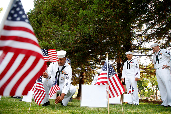 Chief Navy Counselor John Escobedo, left, places flags in the ground next to the Flight 93 Memorial on Monday, Sept. 11, 2017, in Union City. The flags were placed to honor law enforcement members who were killed during the attacks on September 11, 2001. Photo by Aric Crabb, Bay Area News Group