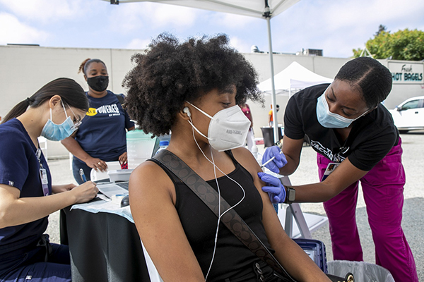 Keoni Gist, an RN with Kaiser Permanente, gives a coronavirus vaccination shot to Kaylan Black, a 16-year-old Envision Academy student, Saturday, July 31, 2021, at a clinic co-sponsored by Beebe Memorial Cathedral in Oakland. Photo by Karl Mondon, Bay Area News Group