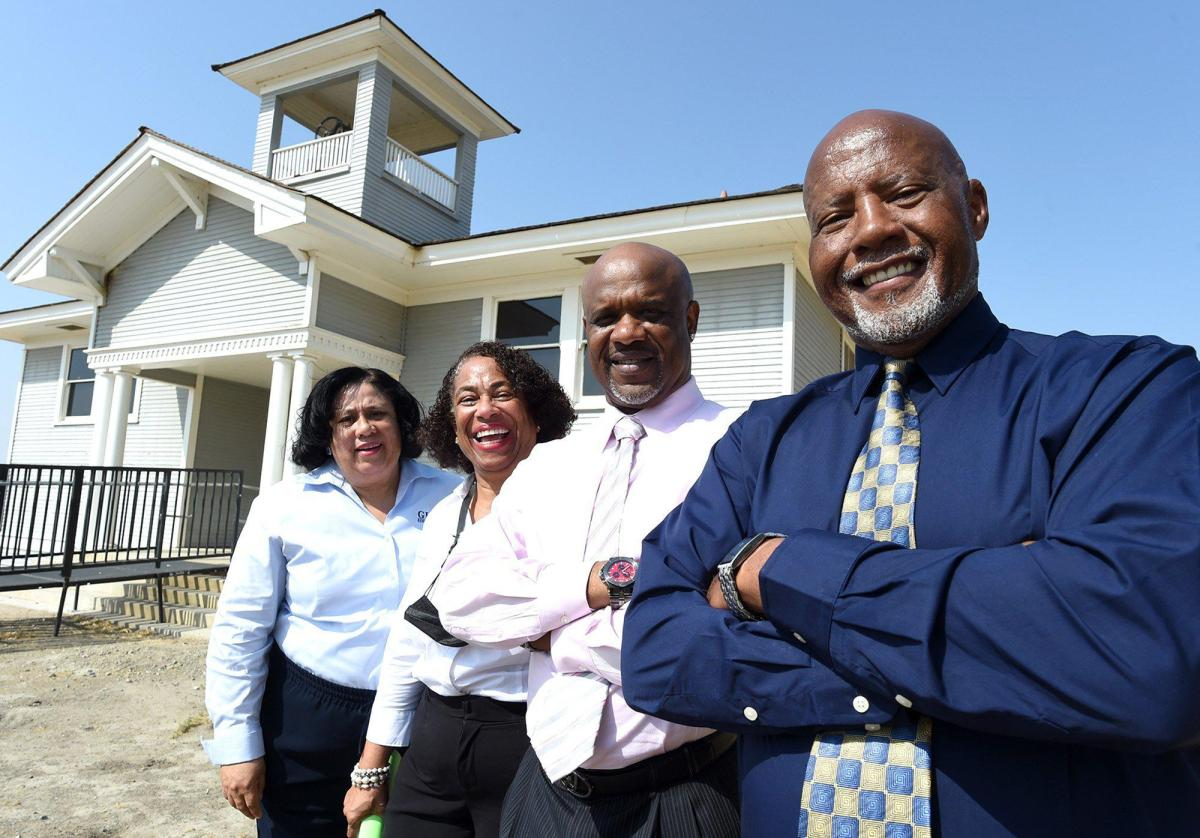 In front of the 1912 Allensworth schoolhouse, officials of the Global Economic Impact Group, LLC, left to right, Randall Cooper, CEO, William Broomfield, COO, Cynthia Sterling, Director of Public Affairs, and Gail Crooms, Planner of Operations, at the rededication and relaunching of the Allensworth State Historical Park, Wed. Aug. 26, 2021. The group is seeking to revitalize the park, the site of the town of Allensworth, founded in 1908 by Colonel Allen Allensworth, the first town in California established exclusively by African Americans. Photo by John Walker, The Fresno Bee