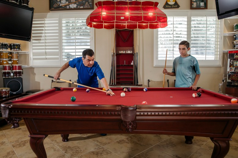 Dr. Shura Alexis Moreno plays pool with his son Gabriel Alejandro Moreno at their home in Alta Loma on Sept. 13, 2021. Dr. Moreno was one of the COVID-19 patients to receive a lung transplant. Photo by Jessica Pons for CalMatters