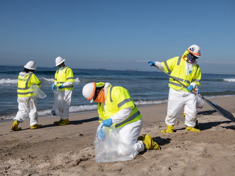 Crew members look for oil clusters along the sand in Huntington Beach on Oct. 5, 2021. An oil spill was reported on Oct. 2, which originated from a pipeline near the coastal grounds off Huntington Beach. The rupture has leaked nearly 126,000 gallons of crude, threatening ecological reserves such as, the Talbert Marsh wetlands in Huntington Beach. Photo by Pablo Unzueta for CalMatters